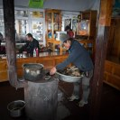 The stove is filled with yak dung as people sit around the dining room.